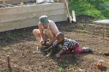 Su Freytag zeigt einem Buben aus Eritrea, wie man pflanzt und wässert. Fotos: Sonja Fasler Hübner